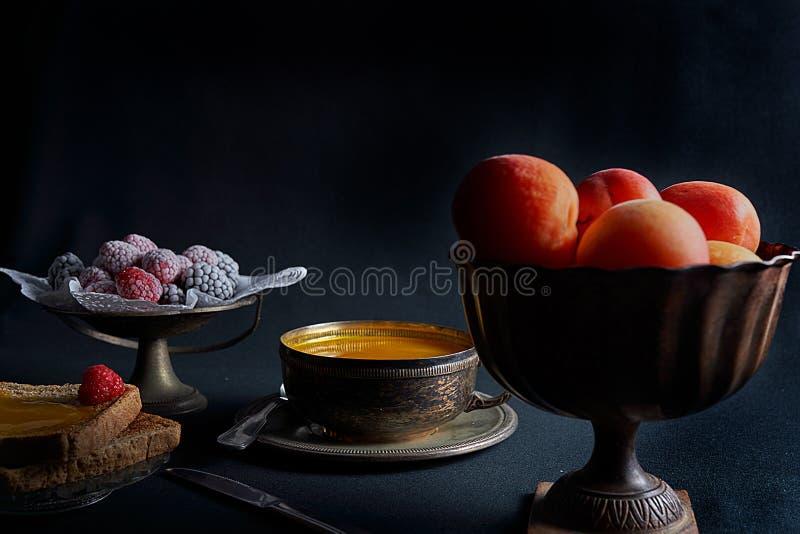 De verse abrikozen, eigengemaakte abrikozenjam, roosterden brood, braambessen en frambozen stock foto