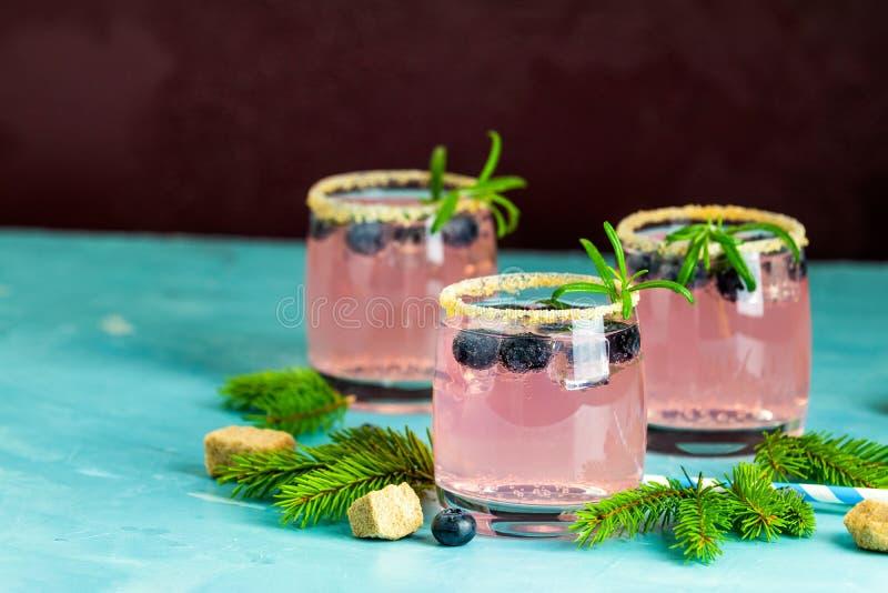 De verse bosbessencocktail met rozemarijn en het ijs in glazen met verfraaien bruine suiker op turkooise oppervlakte en zwarte ac royalty-vrije stock afbeelding