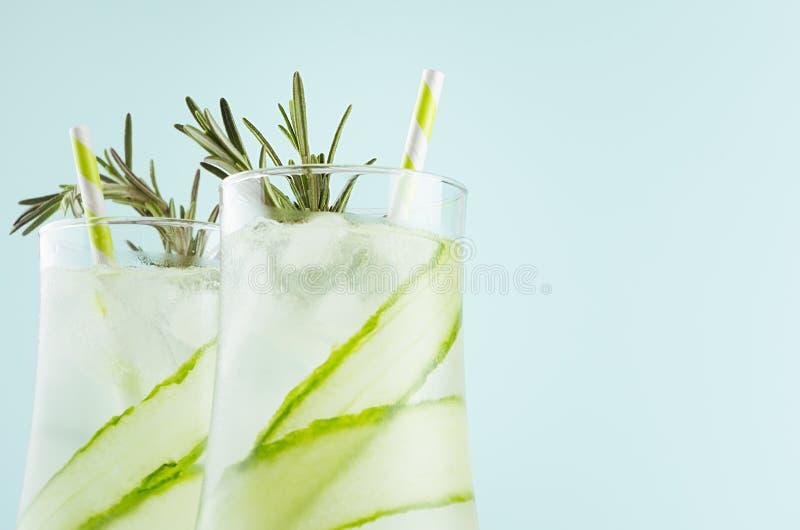 De verse citrusvruchten modderige limonade met ijsblokjes, stro, rozemarijn in elegant misted glazen op zachte lichtgroene achter royalty-vrije stock foto's