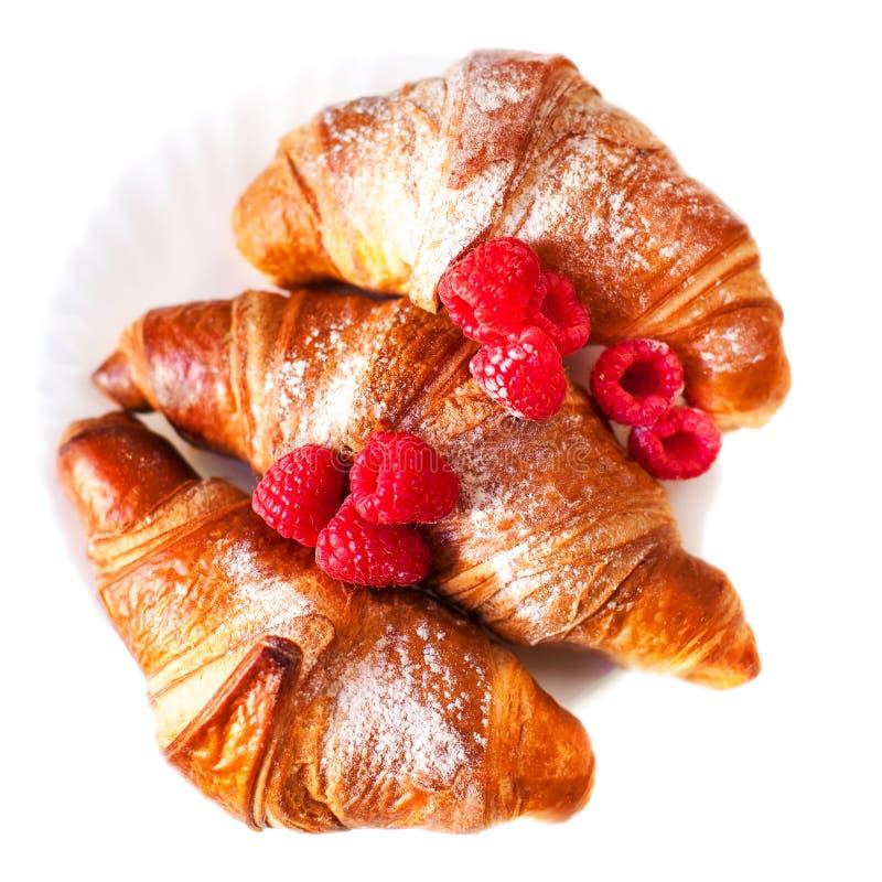 De verse gouden croissants met frambozen sluiten omhoog op wh stock fotografie