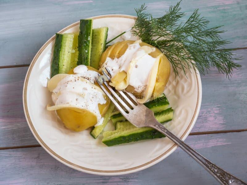 De verse jonge gebraden die aardappels, met kaas worden gevuld, een twijg van verse dille en plakken van groene komkommer liggen  royalty-vrije stock afbeelding