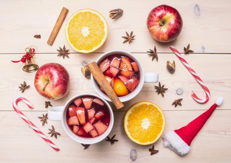 De verse Kerstmisdrank overwoog wijn, appel, sinaasappel, kaneel en kruidnagels, volgende uitgespreide ingrediënten, suikergoed,  stock foto's