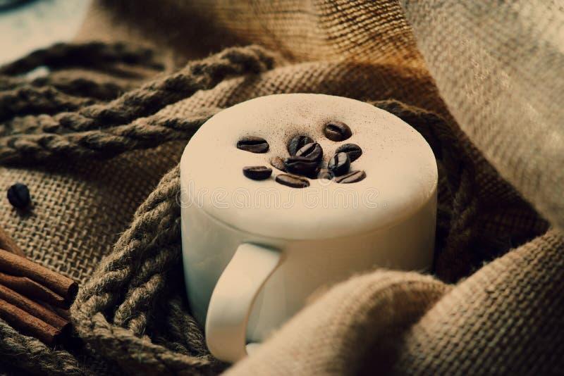 De verse kop van de cappuccinokoffie met kabel, kaneel en koffiebonen op jutezak royalty-vrije stock foto's