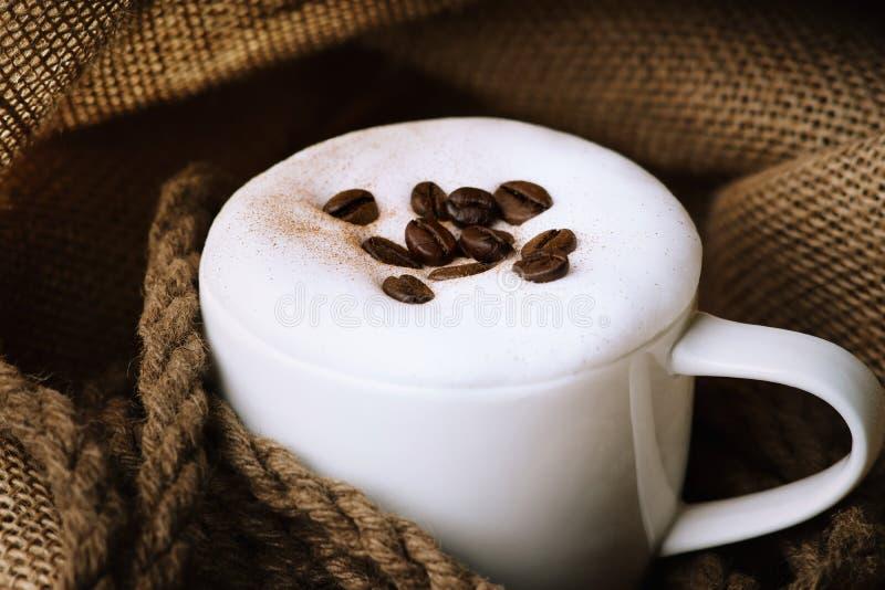 De verse kop van de cappuccinokoffie met koffiebonen op jutezak stock afbeelding