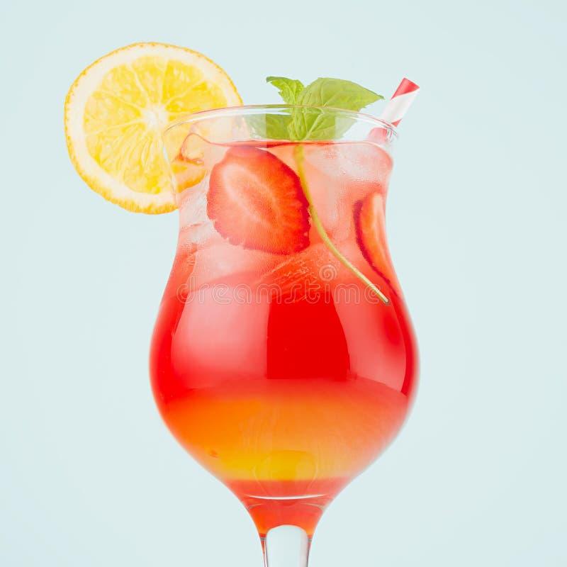 De verse koude zonsopgang van de alcohol gestreepte drank met sinaasappel, aardbei, ijs, munt op groene kleurenmuur, vierkant, cl stock fotografie