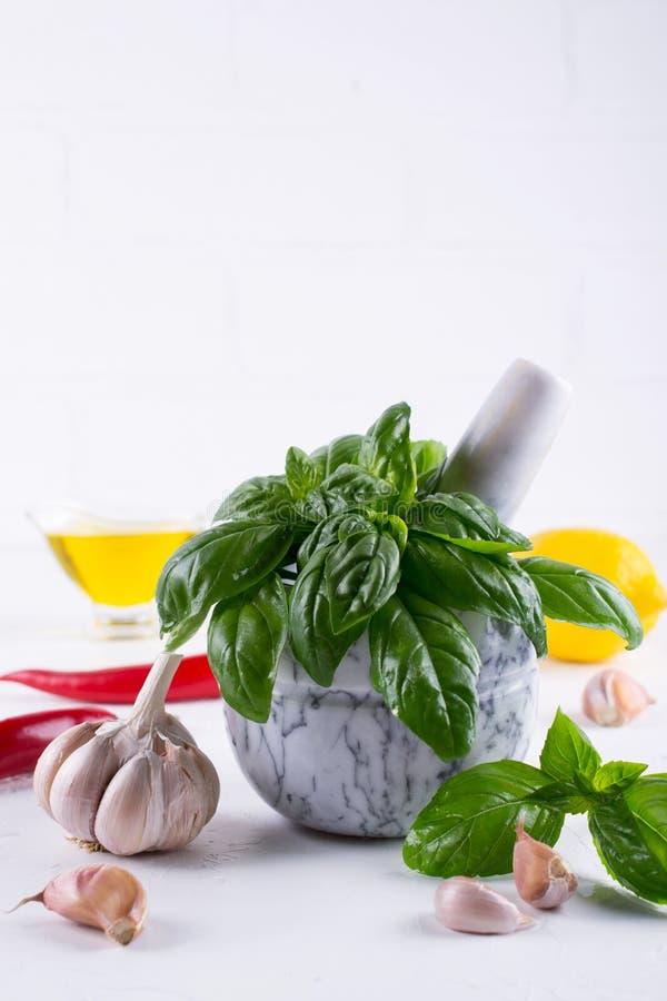 De verse kruiden van het tuinbasilicum in mortier en olijfolie, knoflook, roodgloeiende Spaanse peperpeper, citroen stock fotografie