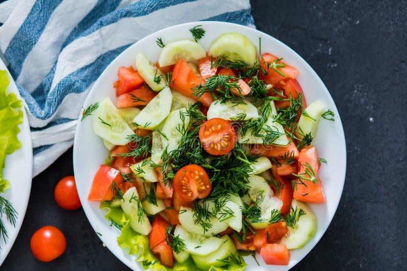 De verse de lente plantaardige salade van tomaat en de komkommer op een zwarte achtergrond, sluiten omhoog stock foto