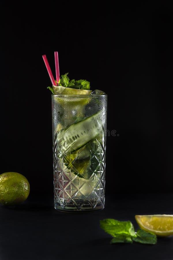 De verse limonade van de de zomerkomkommer met twee roze stro in het glas Zwarte achtergrond Kalk en munt op de lijst stock afbeelding