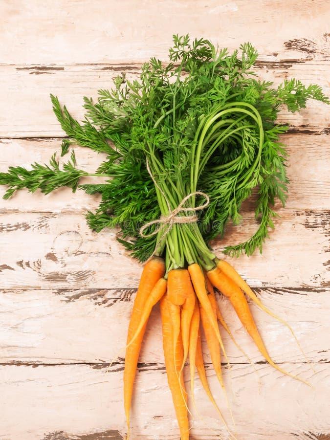 De verse natuurlijke organische wortelen bundelen lichte houten achtergrond De oogstconcept van de de herfstzomer Rustieke natuur royalty-vrije stock foto's