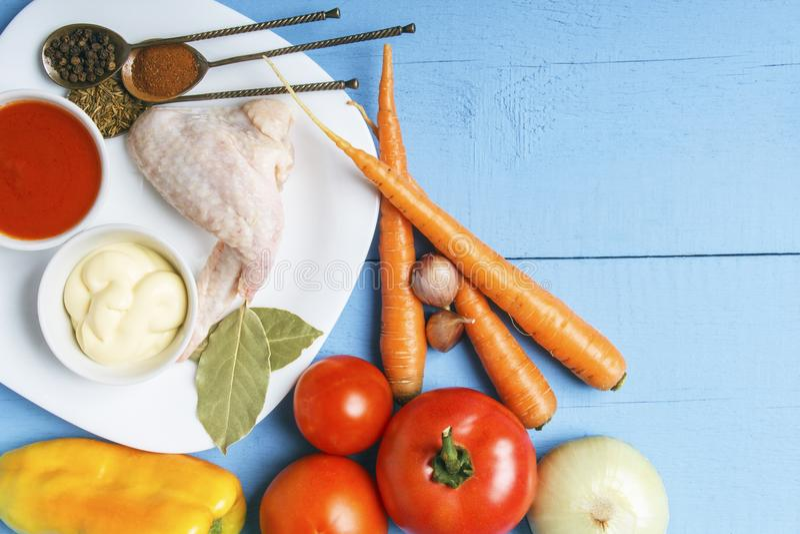 De verse organische groenten van rustieke tuin voor dieet versieren en ruwe kippenvleugels op witte plaat Hoogste mening over hou royalty-vrije stock foto