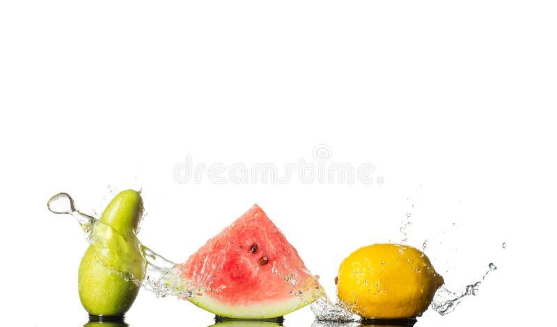 De verse Plons van Tomaten Peer, watermalon en citroen met watergolf op witte achtergrond wordt geïsoleerd die stock foto's