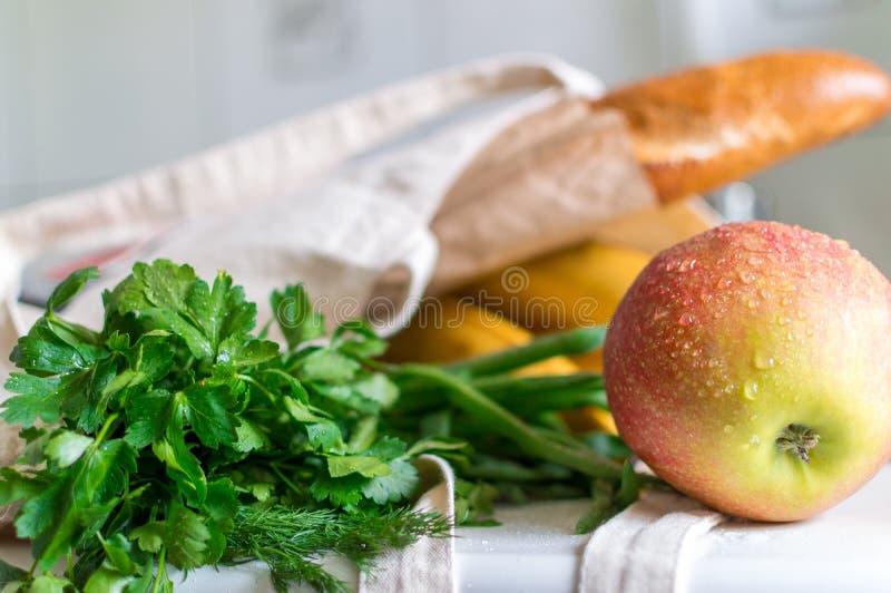 De verse rijpe appel, de bos van peterselie en groene ui, de bananen en Franse baguette in totalisator van de canvas de opnieuw t stock afbeeldingen