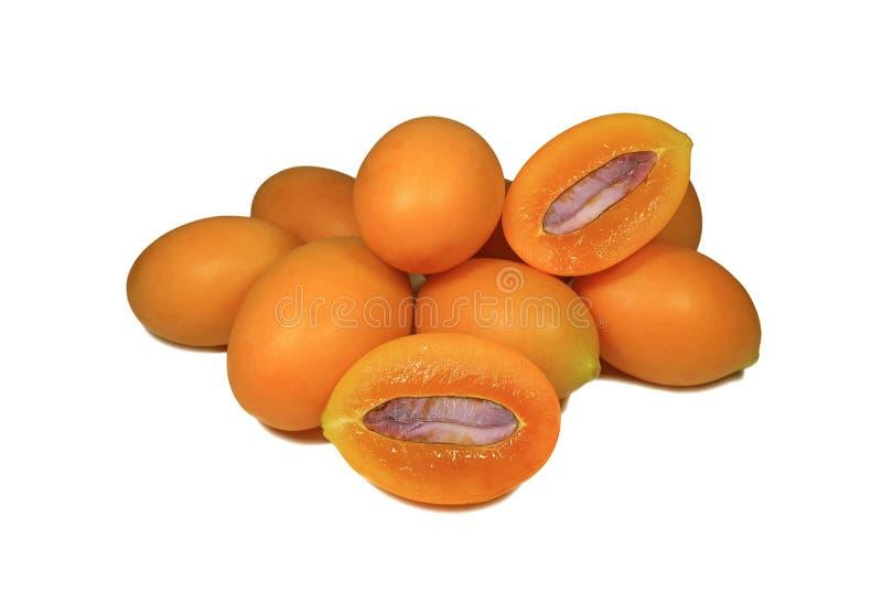 De verse rijpe geeloranje gehele vruchten en de besnoeiing van kleurenmarian plums in halve vruchten met purper zaad op witte ach royalty-vrije stock fotografie