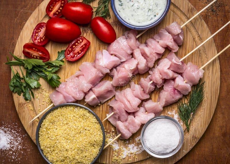 De verse ruwe gesneden borst van Turkije op vleespen met bulgur, met tomatensaus en kruiden met zout op een scherpe raad op een h royalty-vrije stock foto's
