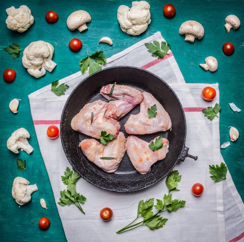 De verse ruwe kippenvleugels in de oude de bloemkooltomaten van de gietijzerkoekepan schiet en kruiden een wit servet op rustieke royalty-vrije stock foto