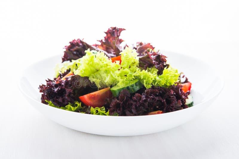 De verse salade met groene en purpere sla, de tomaten en de komkommers op witte houten achtergrond sluiten omhoog stock afbeeldingen
