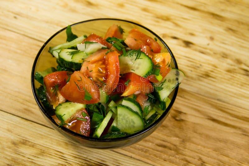 De verse salade met tomaat, de komkommer, de ui, de peterselie en de dille in glas werpen op houten lijst stock foto's