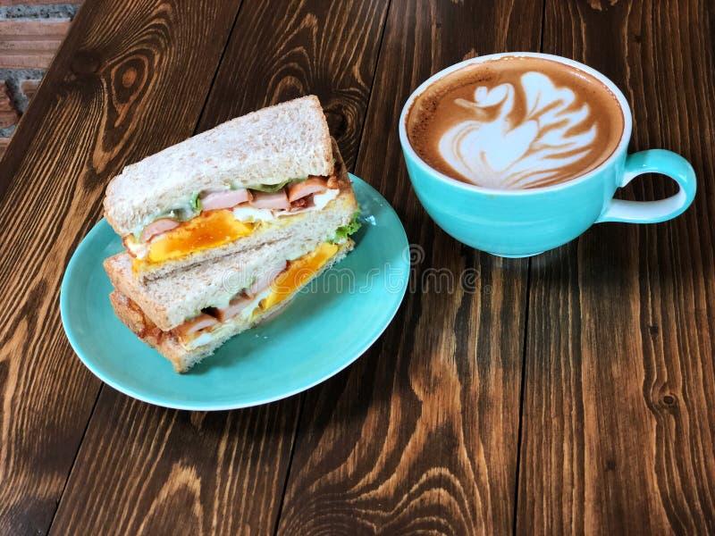 De verse sandwich en zwaan de kunstkoffie van vormlatte vormt op de houten lijst tot een kom royalty-vrije stock afbeelding