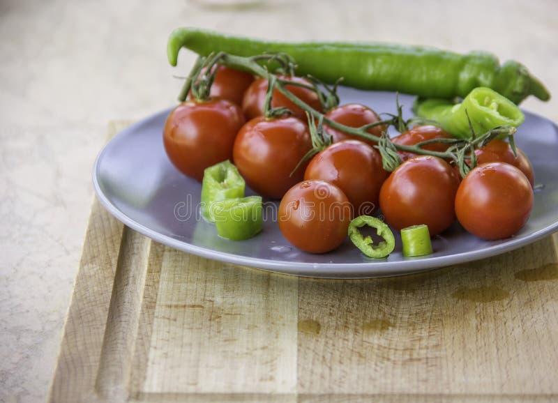 De verse sappige rode plakken van kersentomaten van groene hete peper stock afbeelding