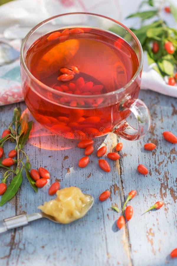 De verse thee van gojibessen in een glaskop op een houten lijst royalty-vrije stock foto