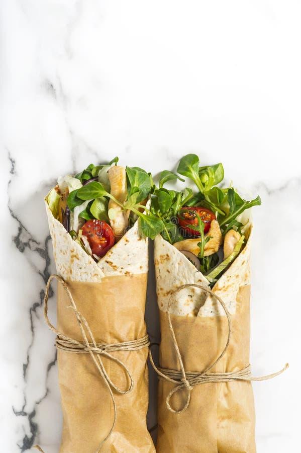 De verse tortillaomslagen op een marmeren patroontafelblad bonden rond met pakpapier en koord stock fotografie