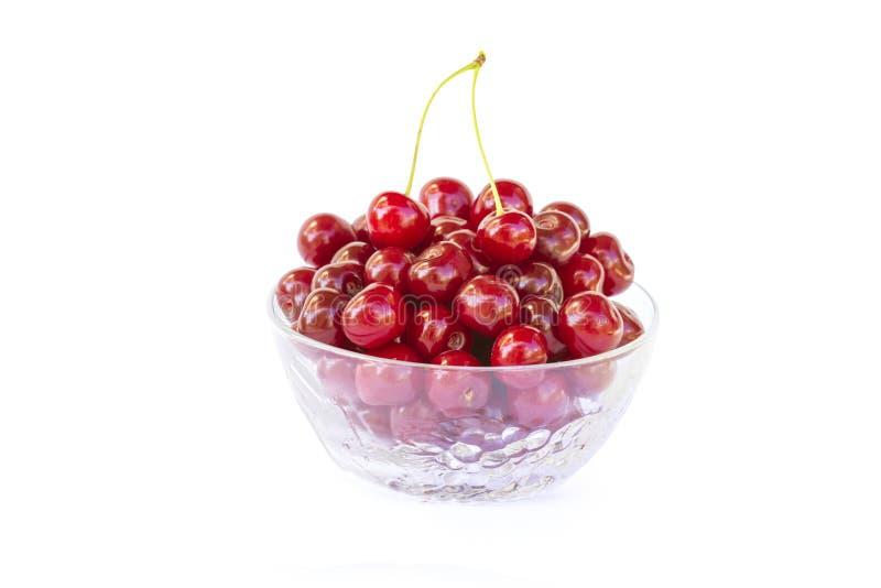 De verse zoete rode kersen in een glas werpen, rijp en sappig kersenfruit, gezond voedsel, close-up, dat op een wit wordt geïsole stock foto