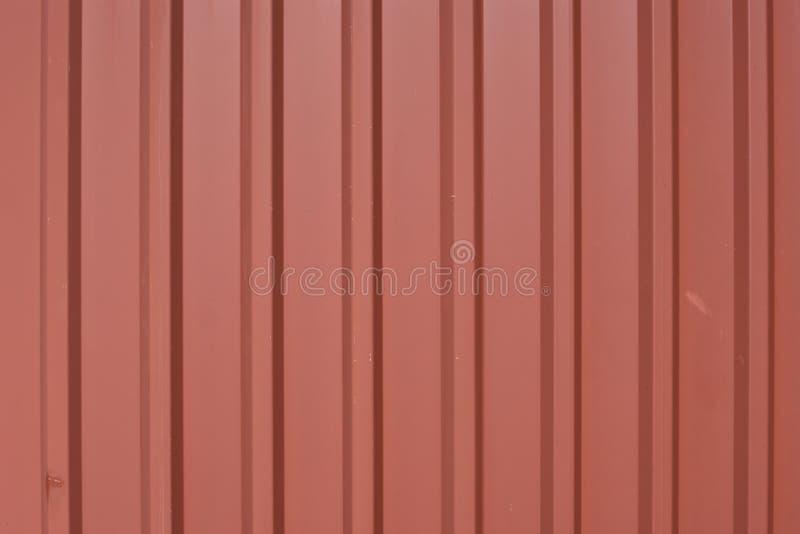 De versleten, golf trapezoïdale metaalpanelen met baksteen rood poeder bedekken en tekens van slijtage en scheur met een laag stock foto