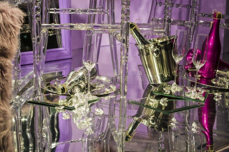 De verspreide stoelen en de glazen, champagneflessen expositie Decoratief show-venster Roze kleuren Ongebruikelijk besluit chaos stock foto