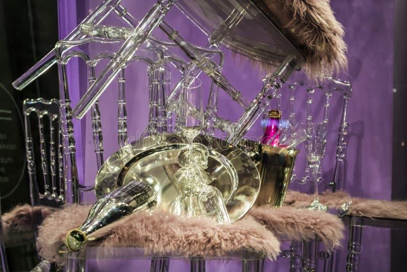 De verspreide stoelen en de glazen, champagneflessen expositie Decoratief show-venster Roze kleuren Ongebruikelijk besluit chaos royalty-vrije stock afbeeldingen