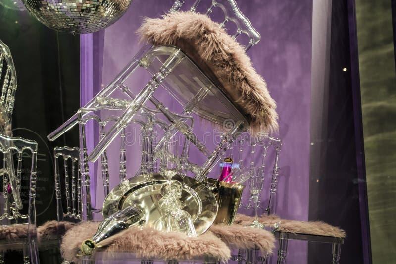 De verspreide stoelen en de glazen, champagneflessen expositie Decoratief show-venster Roze kleuren Ongebruikelijk besluit chaos stock afbeelding