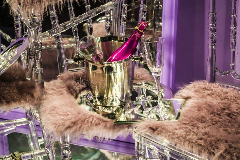 De verspreide stoelen en de glazen, champagneflessen expositie Decoratief show-venster Roze kleuren Ongebruikelijk besluit chaos stock afbeeldingen