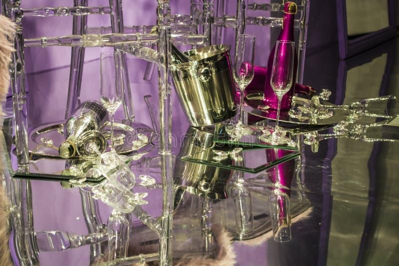 De verspreide stoelen en de glazen, champagneflessen expositie Decoratief show-venster Roze kleuren Ongebruikelijk besluit chaos stock fotografie