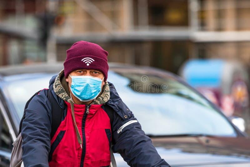 De verspreiding van het virus van de ziekte van Covid-19 in Europa Mensen die een medisch masker dragen tegen het coronavirus, in stock foto