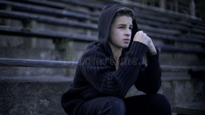 De verstoorde jongen voelt depressie, zittend op stadiontribune, eenzaamheid en verdriet royalty-vrije stock fotografie