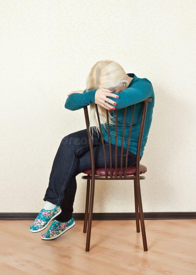 De verstoorde slaap die van de blondevrouw op een stoel zitten stock afbeeldingen