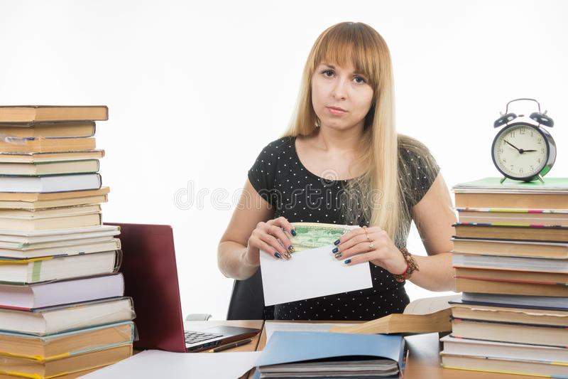 De verstoorde studente zet geld in een envelop om de leraar in het examen om te kopen royalty-vrije stock fotografie