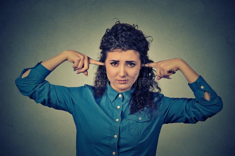 De verstoorde vrouw die oren met vingers stoppen wil niet luisteren stock fotografie