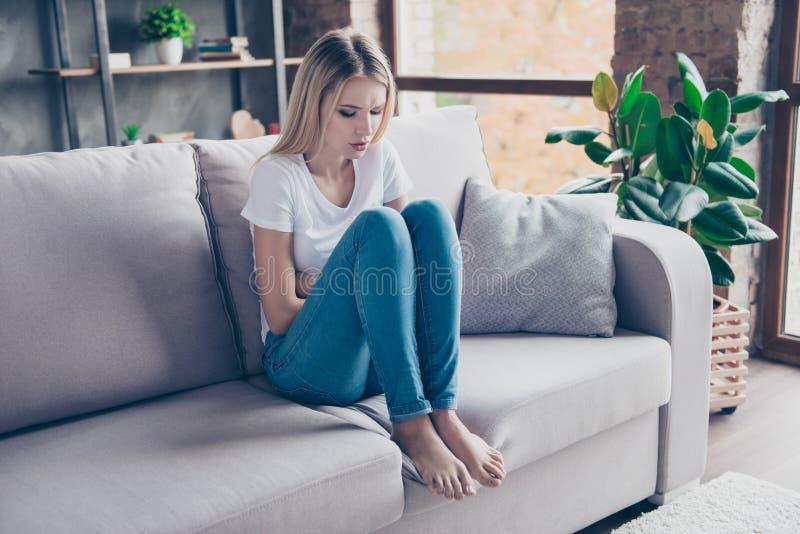 De verstoorde vrouw heeft eerste symptomen van pms Zij zit op een bank stock afbeeldingen