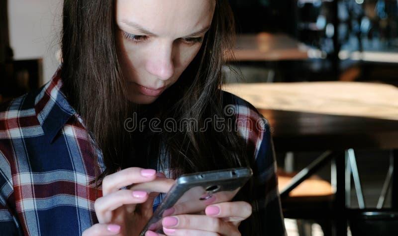 De verstoorde vrouw verzendt een bericht of een gebruik Internet in de telefoonzitting in een koffie Gekleed in een plaidoverhemd royalty-vrije stock foto's