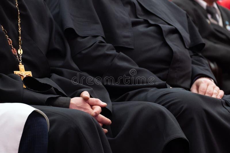 De vertegenwoordigers van de Orthodoxe geestelijkheid in zwarte robes zitten in de conferentiezaal Vergaderingsgeestelijken en pr stock foto's