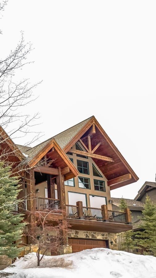 De verticale buitenkant van het kader Mooie die huis door sneeuwy grond en naaldbomen wordt omringd in de winter royalty-vrije stock afbeelding