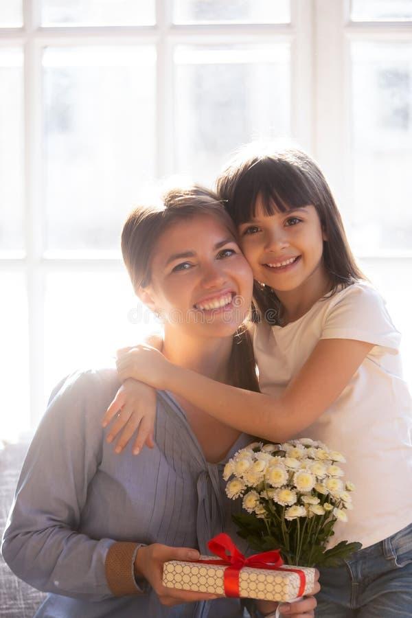 De verticale dochter die van de beeldmoeder de doos en de bloemen van de holdingsgift omhelzen royalty-vrije stock afbeeldingen