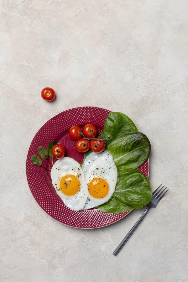 De verticale grens met hart vormde gebraden eieren met groenten op rode plaat met vork op witte achtergrond stock fotografie