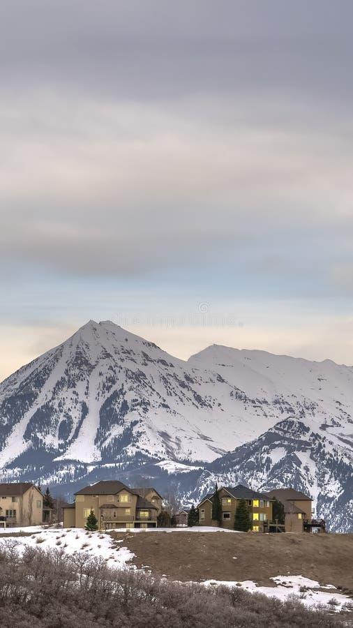 De verticale kaderhuizen met mening van torenhoge sneeuw bereikten berg en donkere hemel in de winter een hoogtepunt royalty-vrije stock afbeeldingen