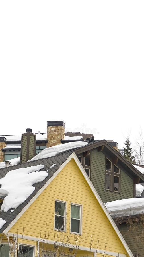 De verticale Sneeuw behandelde daken van woonplaatsen op een berg tegen donkere hemel in de winter stock afbeeldingen