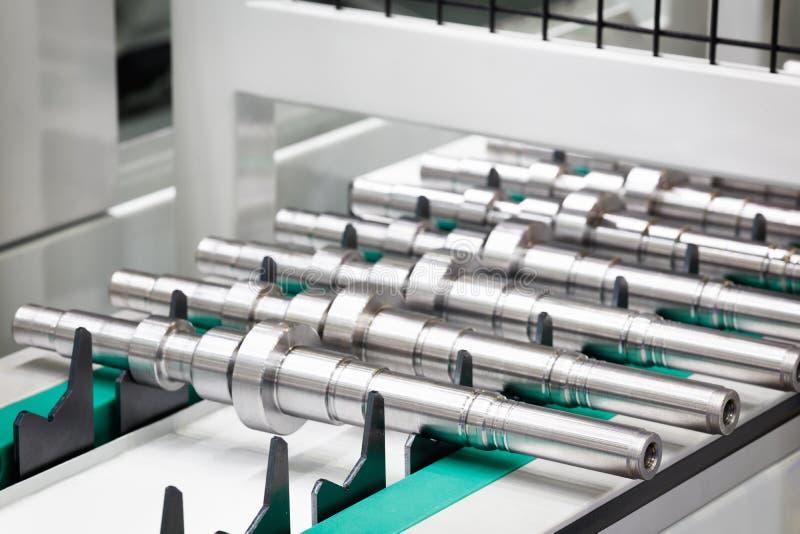 De vervaardiging van metaalproducten, de schachten of de ringen liggen op een transportband, industriële conceptenachtergrond stock fotografie