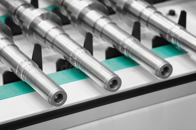 De vervaardiging van metaalproducten, de schachten of de ringen liggen op een transportband, industriële conceptenachtergrond stock afbeeldingen