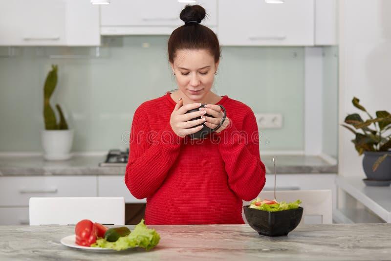 De verwachtende jonge moeder heeft ontbijt bij keuken, eet verse groentesalade en drinkt thee, draagt toevallige rode sweater, he royalty-vrije stock foto's