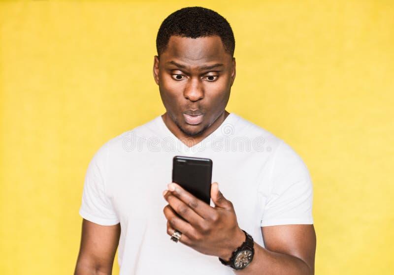 De verwarde en ongerust gemaakte knappe Afrikaanse Amerikaanse mens houdt smartphone, staart met verraste uitdrukking stock afbeeldingen