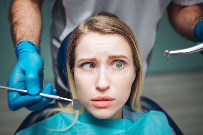 De verwarde jonge vrouw zit als voorzitter in tandheelkunde Zij houdt ogen gerold Tandartstribune achter haar en greephulpmiddele royalty-vrije stock afbeelding
